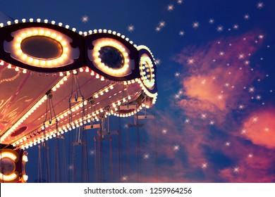 illuminated french carousel at night. toned image