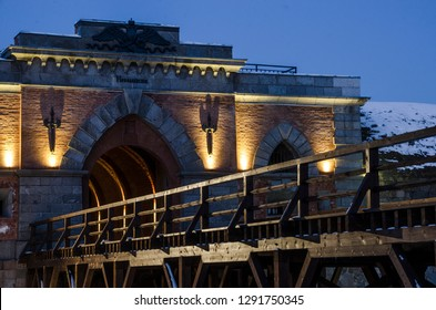 Illuminated gate of Daugavpils fortress with wooden bridge in winter evening