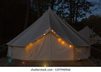 Illuminated glamping bell tent at night