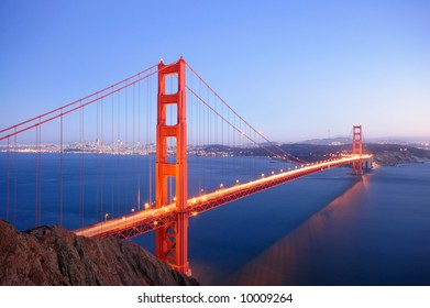 Illuminated Golden Gate Bridge glows in the dusk on an autumn evening.
