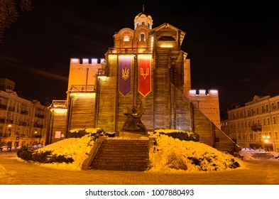 Illuminated Golden Gates and Yaroslav the Wise monument at winter night. Kyiv, Ukraine.