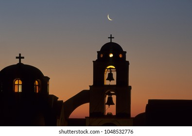 Illuminated greek church at sunset with moon above