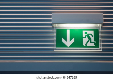 illuminated green emergency exit sign on a modern wall