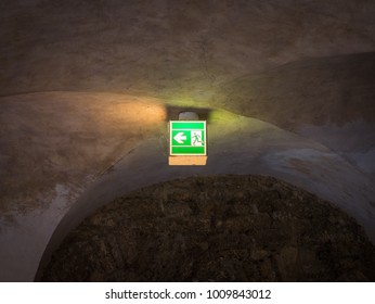 The illuminated green exit sign in dark room