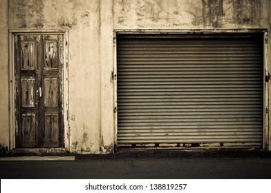 Illuminated grunge metallic roller shutter door near wooden door vintage style.