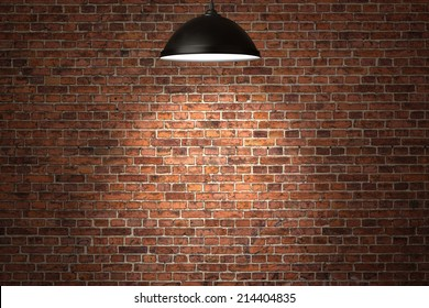 Illuminated grunge red brick wall background with copy space