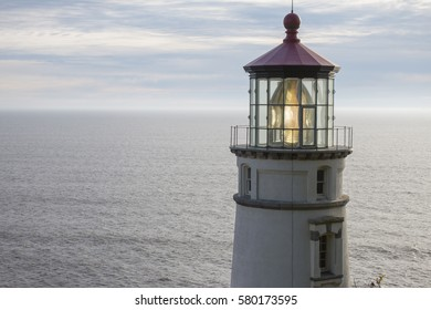 Illuminated Historical Lighthouse with Ocean and Blue Sky Background