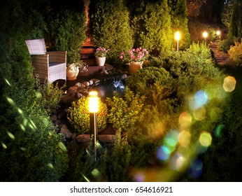 Illuminated home garden patio plants and evening party lights near small fountain