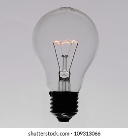 Illuminated incandescent lamp bulb isolated on grey gradient background
