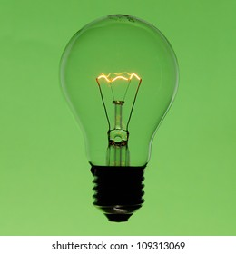 Illuminated incandescent lamp bulb isolated on green gradient background