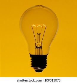 Illuminated incandescent lamp bulb isolated on yellow gradient background