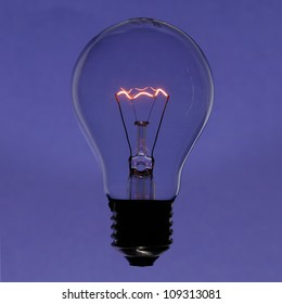Illuminated incandescent lamp bulb isolated on violet gradient background