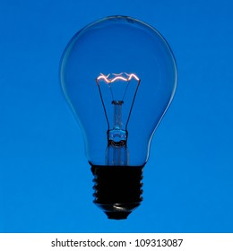 Illuminated incandescent lamp bulb isolated on blue gradient background