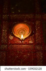 An illuminated Indian clay lamp