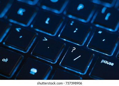 Illuminated keyboard closeup with focus on question. Hi tech concept