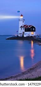 illuminated lighthouse in twilight, light beam shines in dark skies