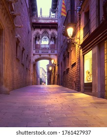 Illuminated medieval street Carrer del Bisbe with Bridge of Sighs in Barri Gothic Quarter, Barcelona, Catalonia, Spain