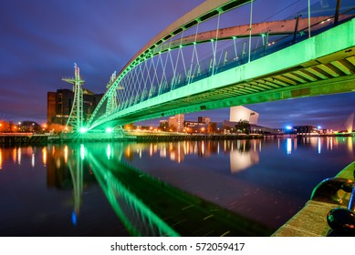 Illuminated Millennium bridge over the Manchester canal in Salford Quays, Manchester, England