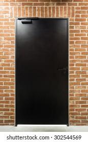 Illuminated modern black door in a brick wall