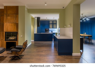 Illuminated modern interior a blue kitchen zone with white tabletops, oven, stove, sink, lockers. There is a leather armchair, fireplace with brown chimney, wooden table with chairs, hanging lamps.