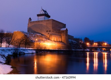 Illuminated Narva castle and reflection in water