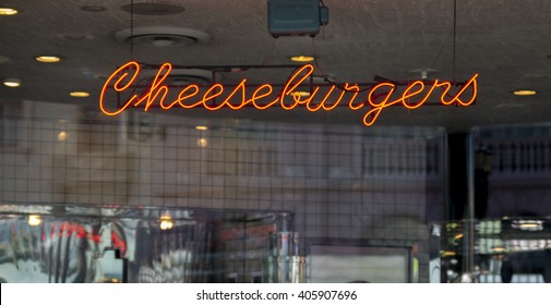 An illuminated neon Cheeseburger sign
