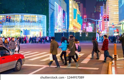 Illuminated with neon night shopping street of Shanghai downtown, crowds of people walking at crossroads, China