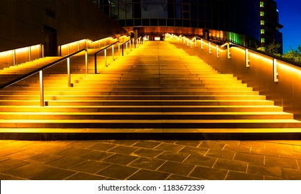 illuminated office building staircase exhaling up to entrance in night city