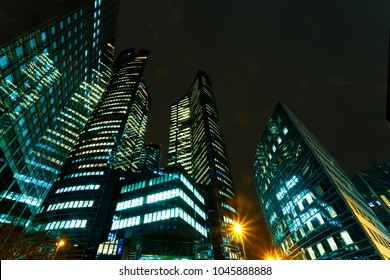 Illuminated office buildings in Paris business district La Defense. Night city lights, skyscrapers glass facades. Modern urban architecture, economy, finances, business activity concept.