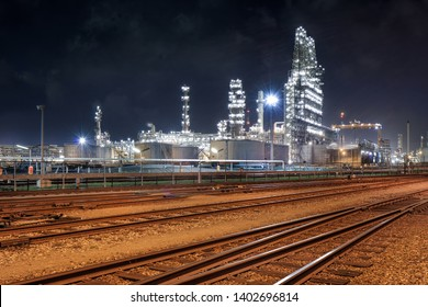 illuminated oil refinery at night with rail tracks on the foreground, Port of Antwerp, Belgium.