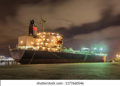 Illuminated oil tanker at night with dramatic clouds, moored at Port of Antwerp, Belgium.