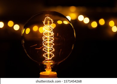 Illuminated old fashioned Edison style light bulb with bokeh of other lights in the background using selective depth of field and reflected in the bulb