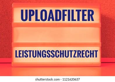 Illuminated panel with the german words Uploadfilter Artikel 13 Leistungsschutzrecht in english Upload filter Article 13 ancillary copyright