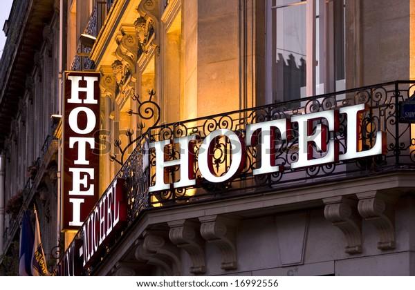 Illuminiertes Pariser Hotelschild aus der Abenddämmerung