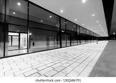 Illuminated pedestrian passage perspective along glass building facade at night