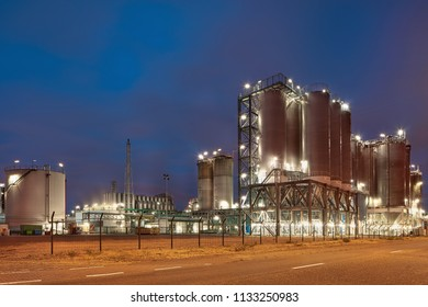 Illuminated petrochemical production plant against a cloudy blue sky at twilight, Antwerp, Belgium.