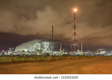 Illuminated petrochemical production plant against a cloudy blue sky at night, Antwerp, Belgium.