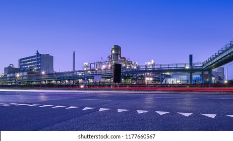 Illuminated petrochemical production plant at twilight in Port of Antwerp industrial area.