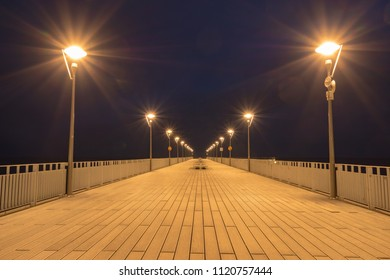Illuminated pier by the sea at night