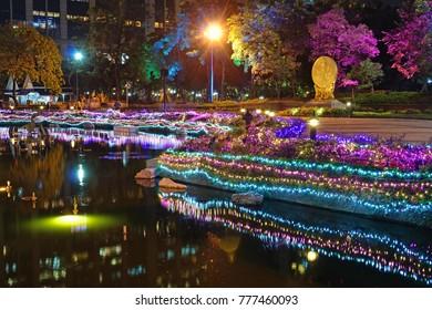 Illuminated pond at Benchasiri Park in Bangkok