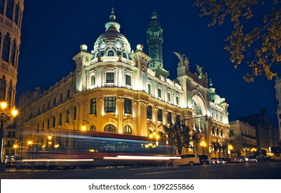 Illuminated post and telegraph building and traffic lights at night, in Valencia. Spain