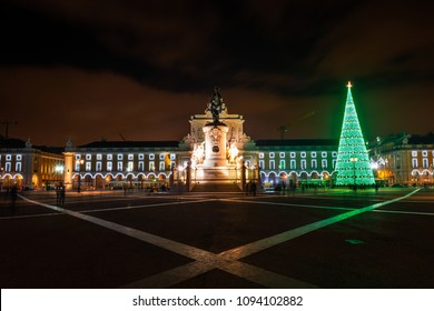 Illuminated Praca do Comercio (Commerce Square) at night in Lisbon, with a modern Christmas tree.
