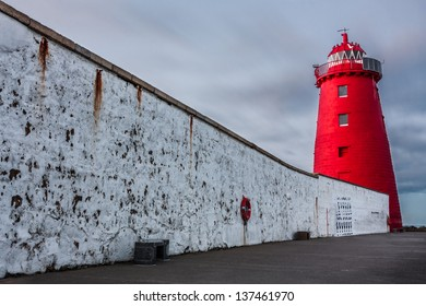 Illuminated red lighthouse and wall against a cloudy sky