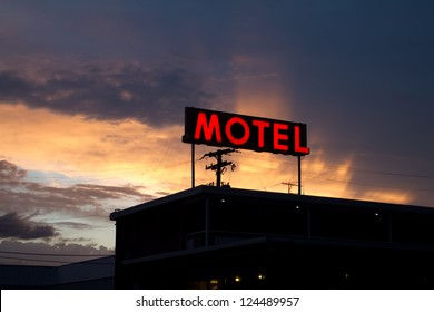 Illuminated red motel sign and motel silhouette, with a brilliant sunset in the background.