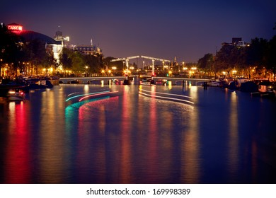 Illuminated and reflected bascule Magere Brug Bridge on Amstel river of Amsterdam, with light trails of boats passing on the water.