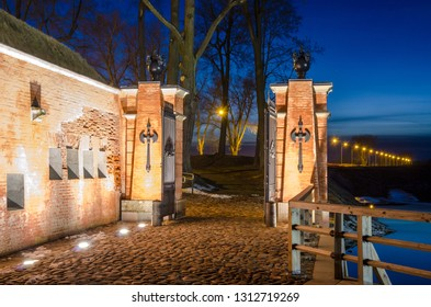Illuminated restored guard house with barrier-gate in Daugavpils Fortress in early spring evening.