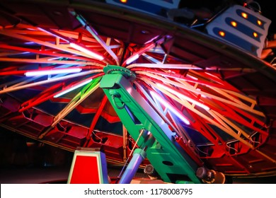 An illuminated rotating circular device in an amusement park.