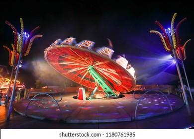 An illuminated rotating circular device in an amusement park.