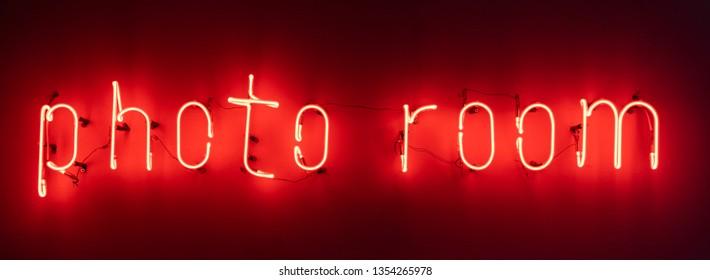 Illuminated signboard saying 'photo room', neon light letters