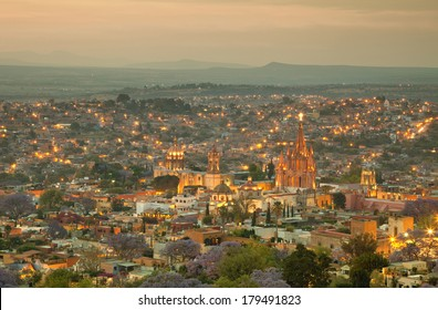 Illuminated skyline of San Miguel de Allende in Mexico after sunset, with a yellow filter effect.